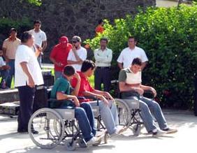 foto de tres personas en sillas de ruedas simulando discapacidad motriz durante charla de sensibilización